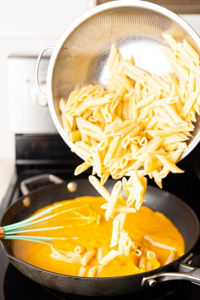 Dumping cooked pasta into a skillet of pumpkin cream sauce.