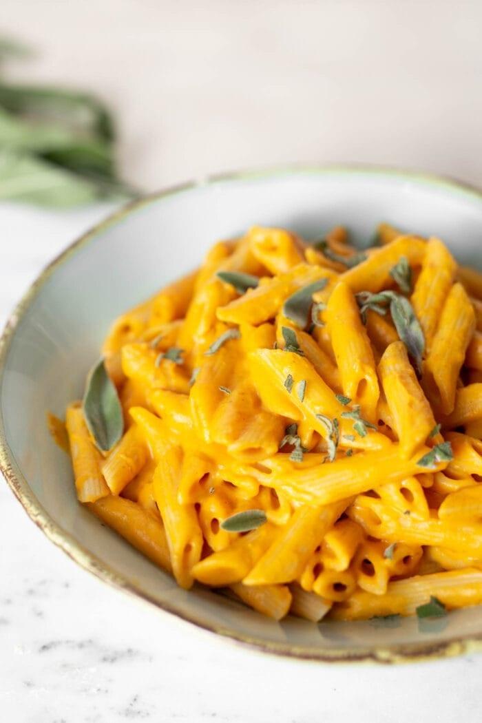 A white bowl of creamy vegan pumpkin pasta.