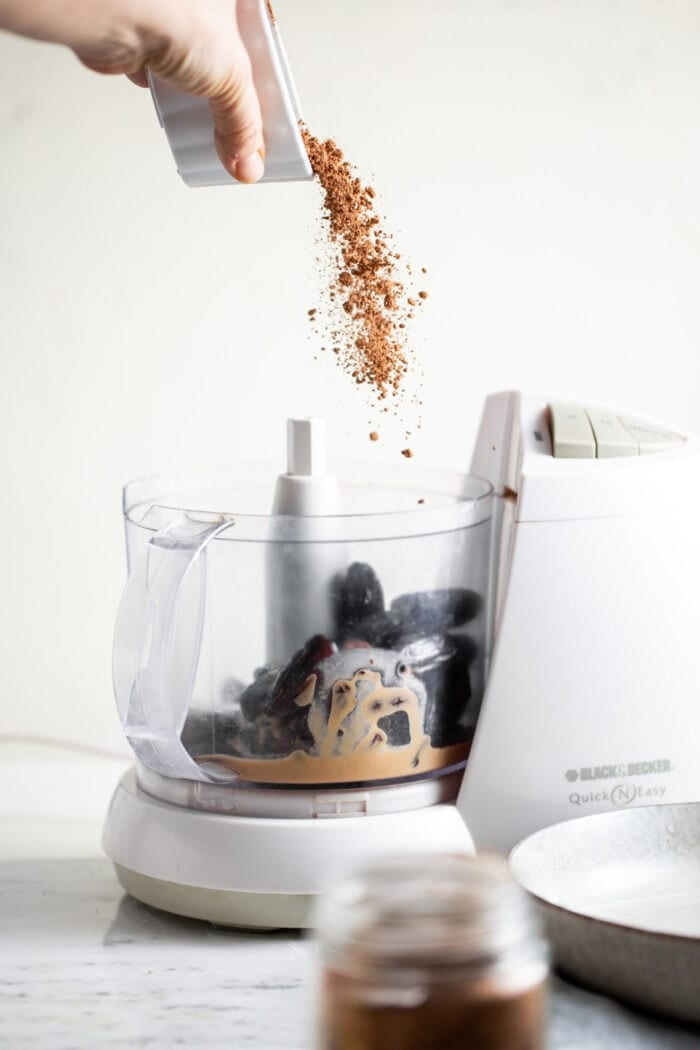 Cacao powder being dumped into a food processor.