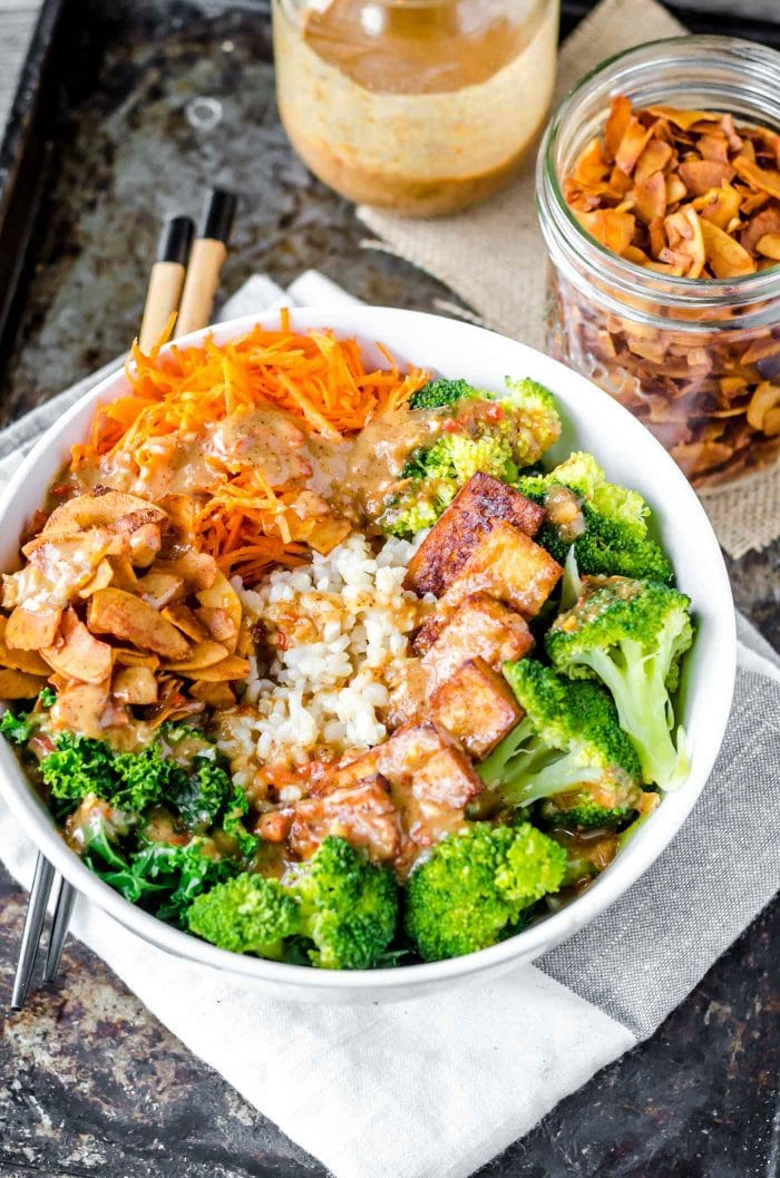 Vegan almond satay bowls with broccoli, brown rice, coconut bacon and tofu.