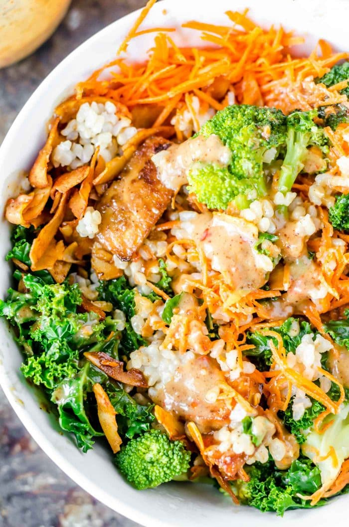 Vegan broccoli and brown rice bowls with coconut bacon, carrot and almond satay sauce.