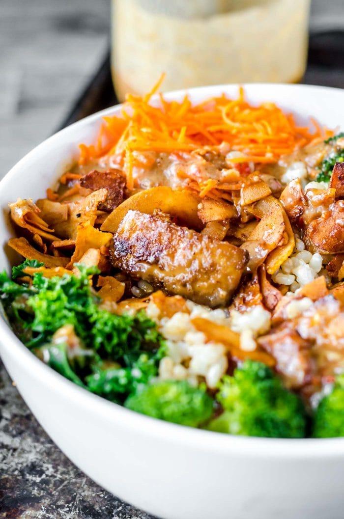 Crispy tofu with almond satay sauce in a vegan buddha bowl.