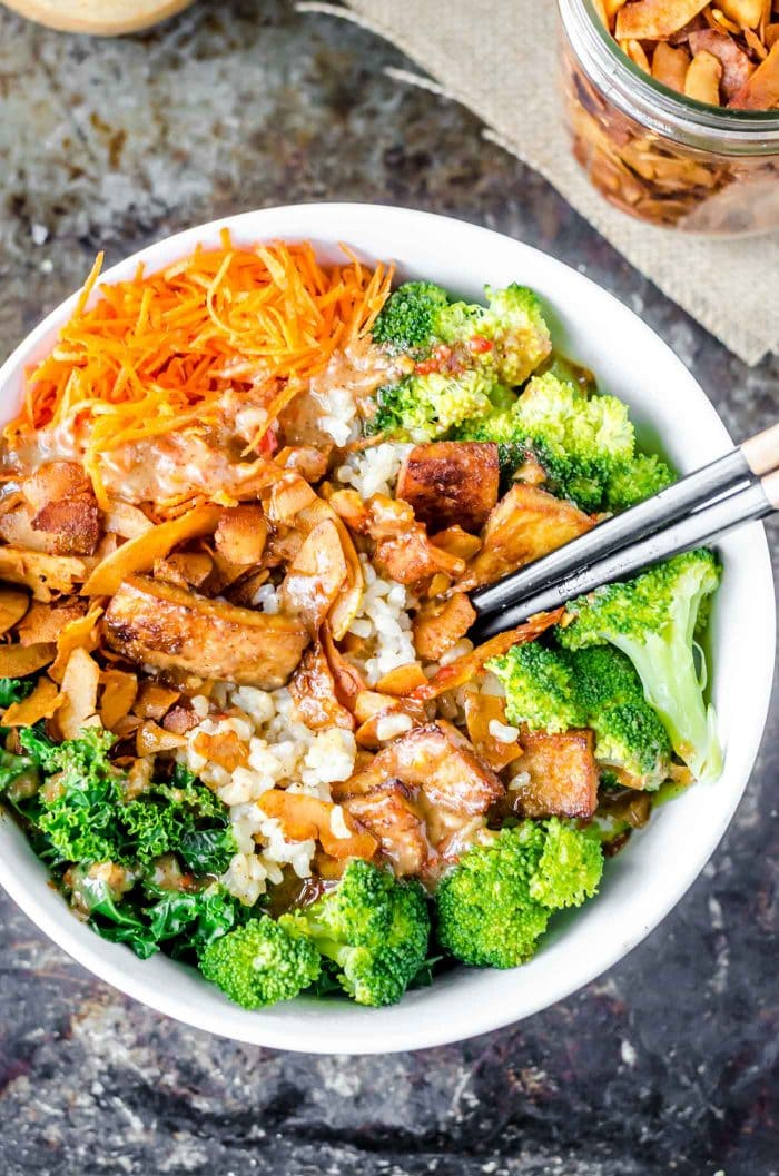 Broccoli and brown rice with chop sticks in a white bowl.
