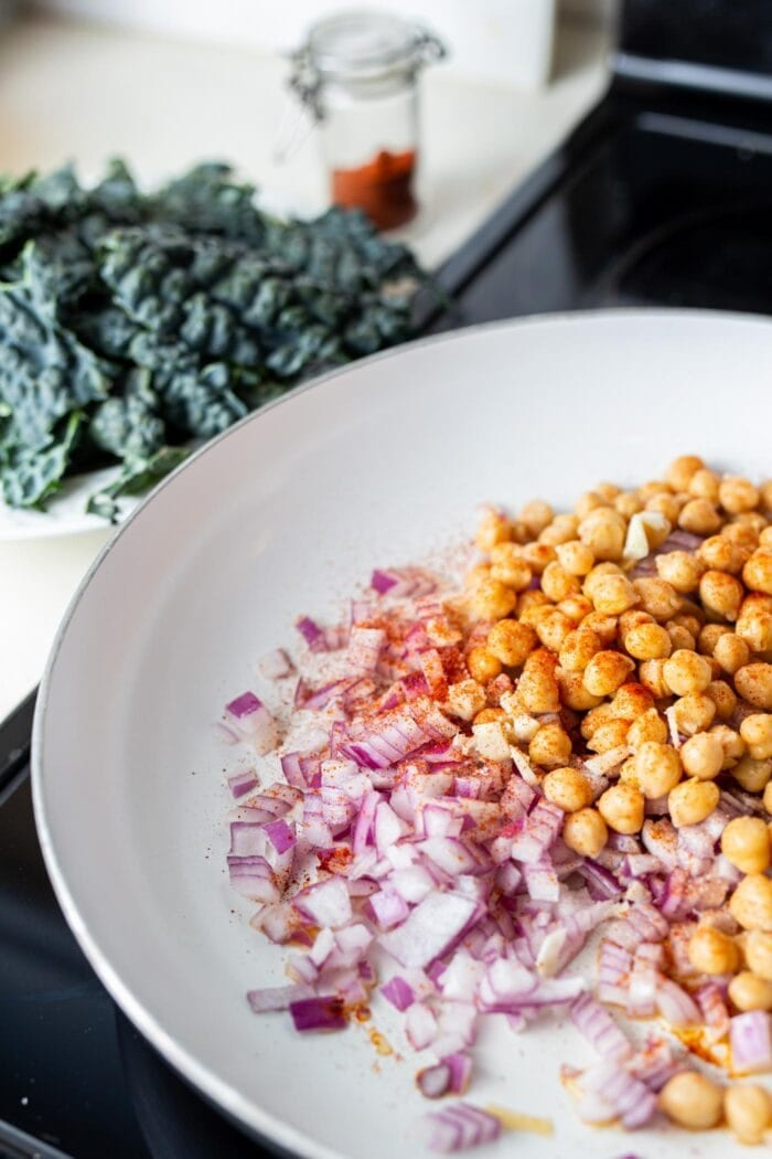 Red onion and chickpeas in a skillet on the stovetop.
