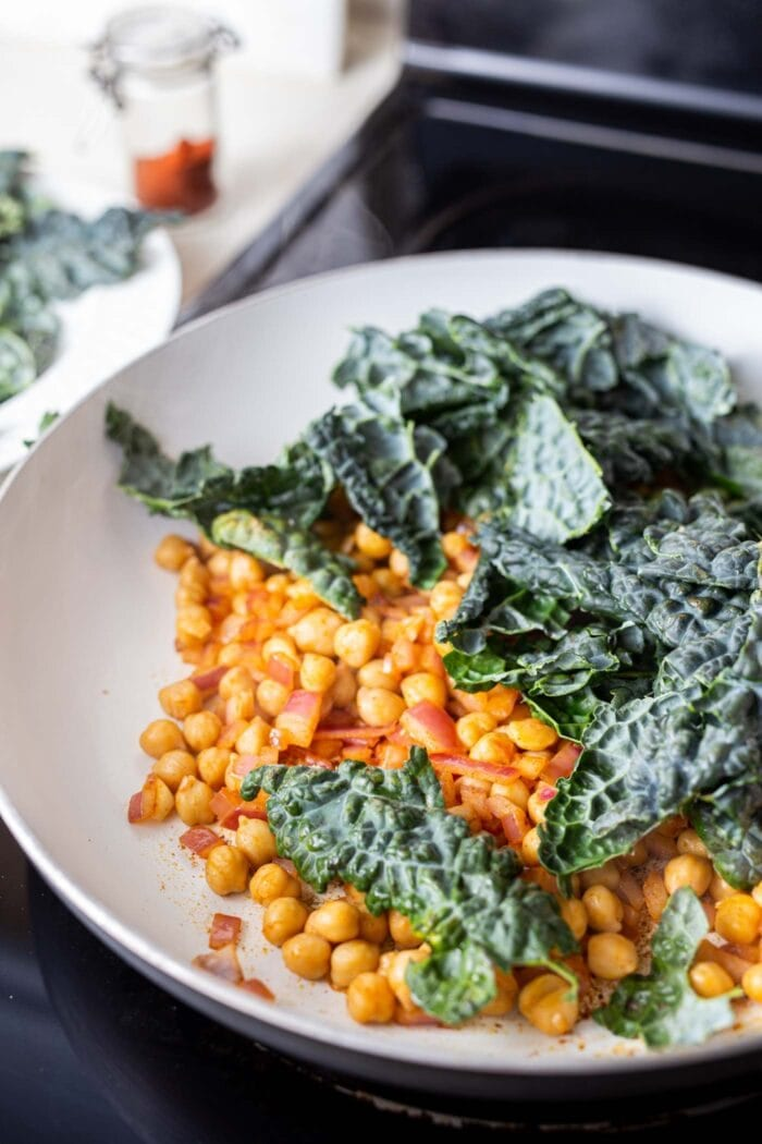 Chickpeas and kale in a skillet on the stovetop.