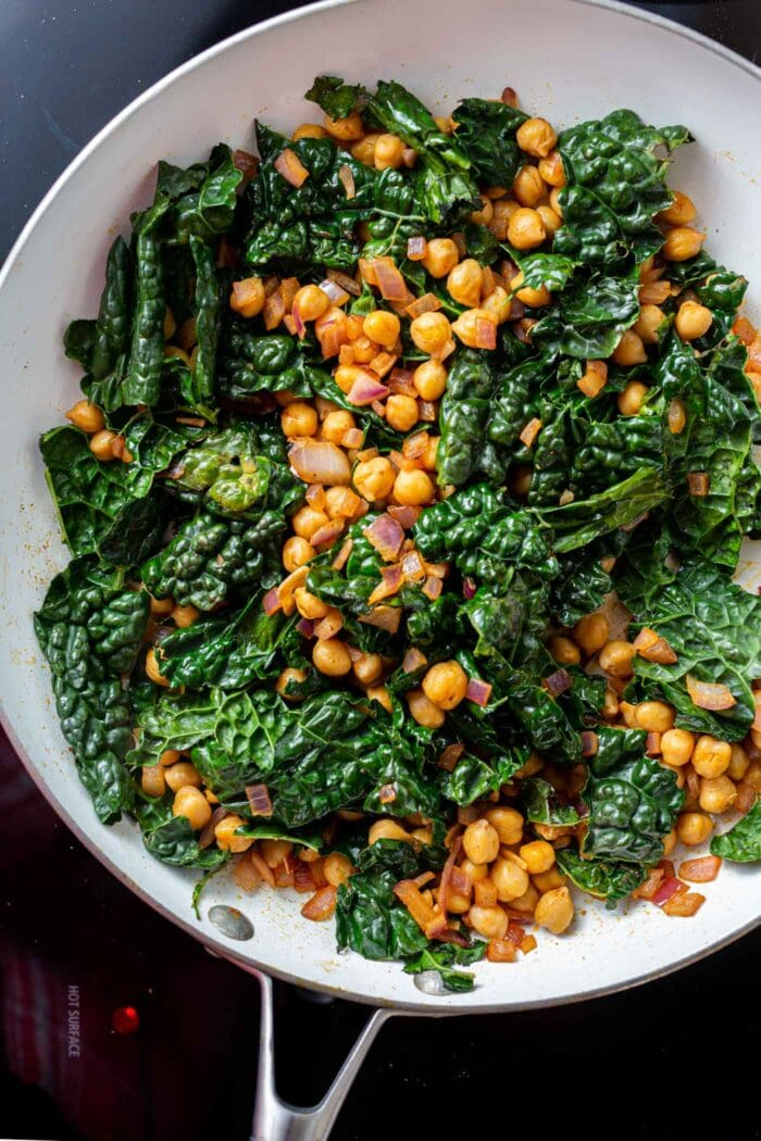 Kale chickpea stir fry in a skillet on the stovetop.