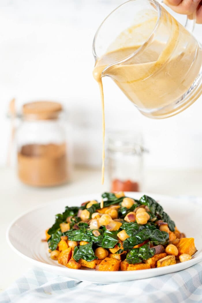 Pouring miso peanut sauce over kale and chickpea stir fry in a white bowl.