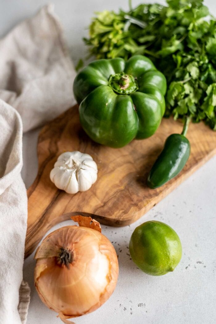 A bell pepper, jalapeno, bulb of garlic, onion and cilantro on a cutting board.