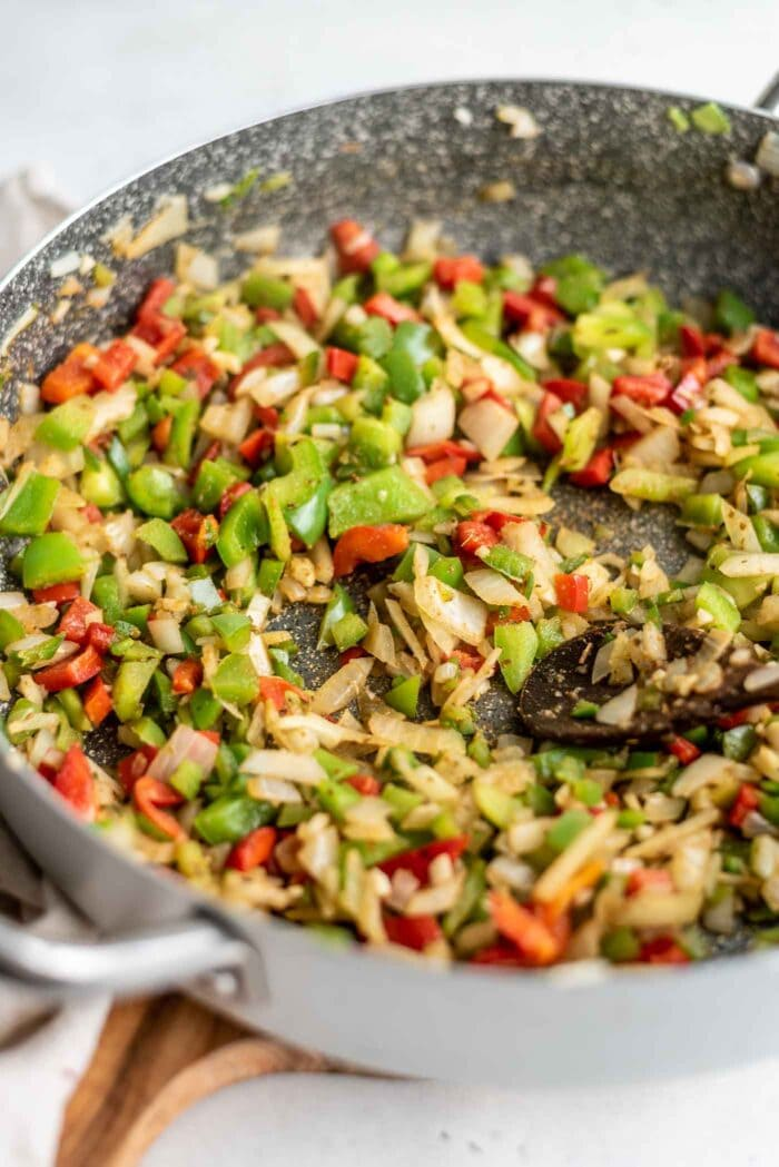 Diced bell peppers, onions and garlic cooking in a large skillet.
