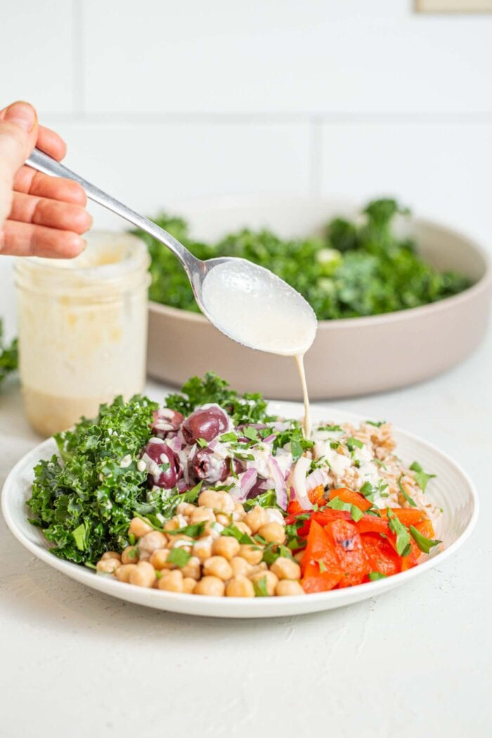 Drizzling tahini over a bowl of farro, kale, roasted red peppers and chickpeas.