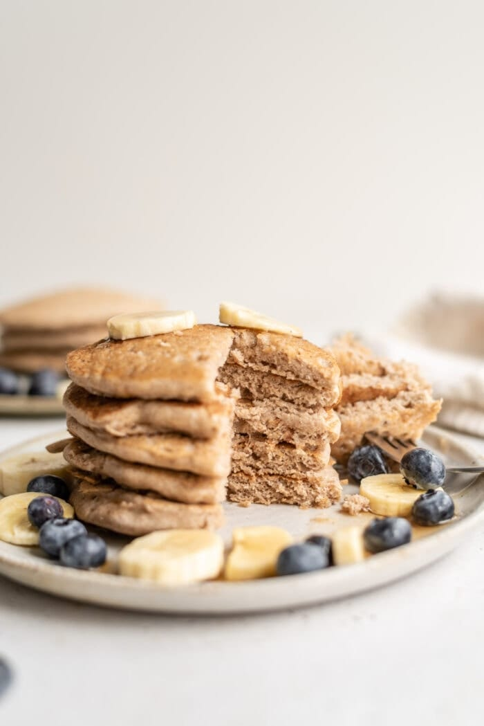 A sliced stack of buckwheat pancakes topped with blueberries and banana on a plate.