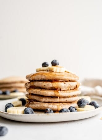 A stack of buckwheat pancakes on a plate, topped with blueberry, banana and syrup.