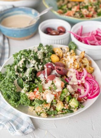 A bright bowl of healthy ingredients pickled onions, cauliflower, quinoa, kale and olives.