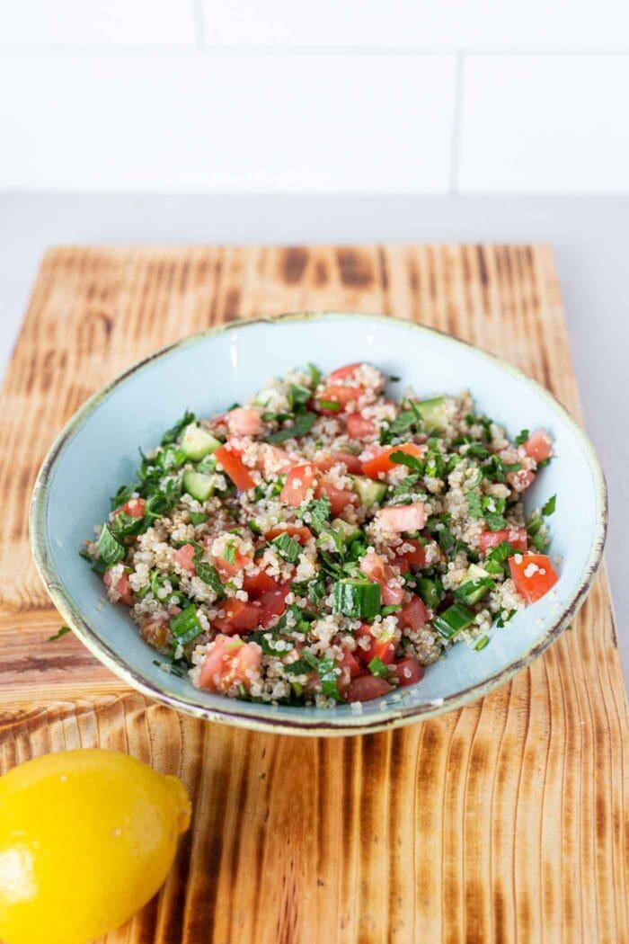 Quinoa tabouli salad in a bowl on a cutting board.