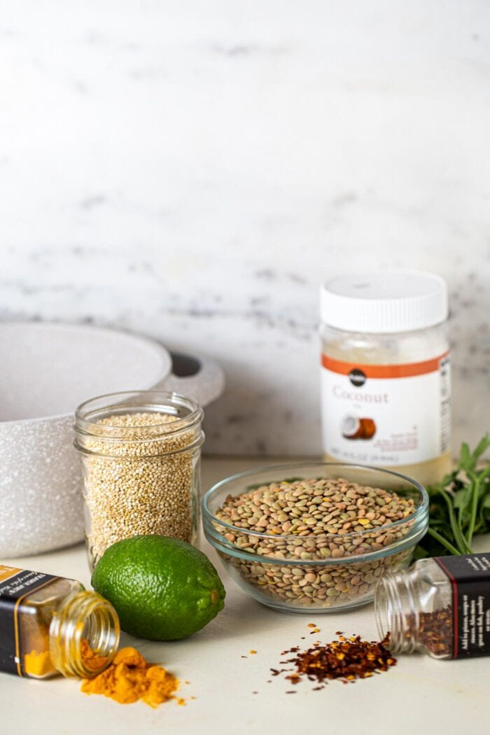 A bowl of lentils, container of quinoa, a lime and a few containers of spices sitting on a counter top.