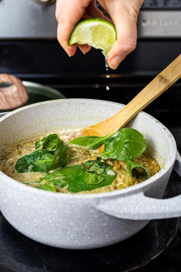 Squeezing lime juice into a pot of lentils, quinoa and spinach on the stovetop.