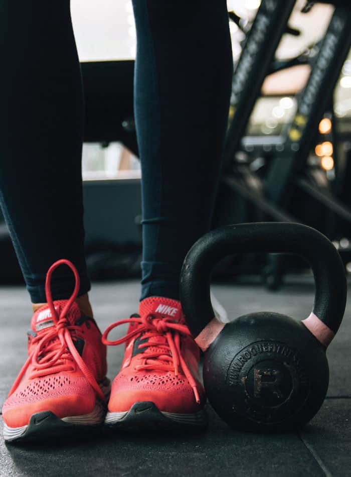 The lower half of someone's legs in running shoes standing beside a kettlebell.