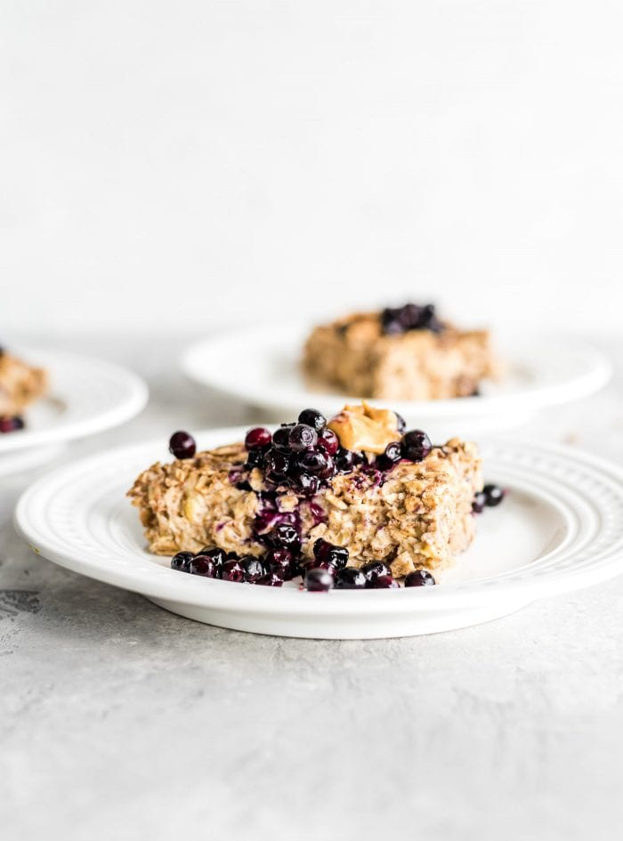 Easy banana baked oatmeal topped with berries and peanut butter on a white plate/