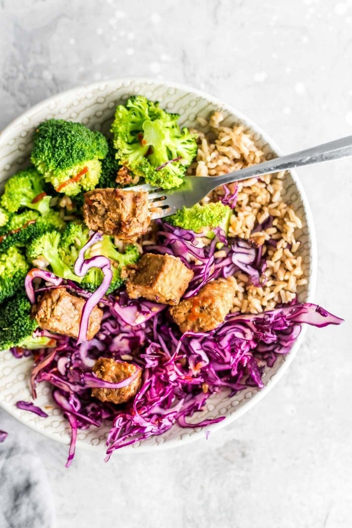 Mixed red cabbage, baked tempeh, brown rice and steamed broccoli in a bowl with a fork.