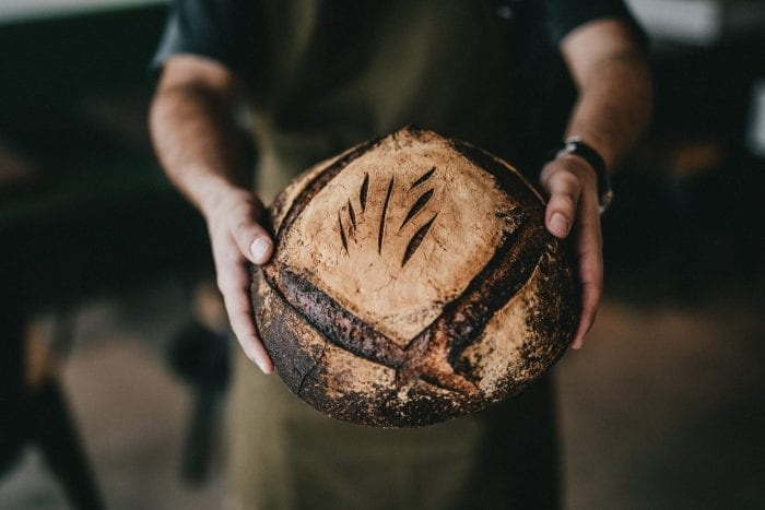 Hands holding a fresh baked loaf of bread.