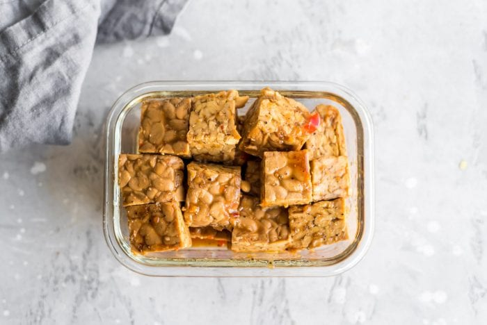 Chopped marinated tempeh in glass container.