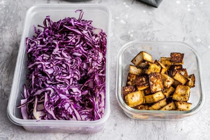 One container with shredded purple cabbage and one container with baked tofu for vegan meal prep.