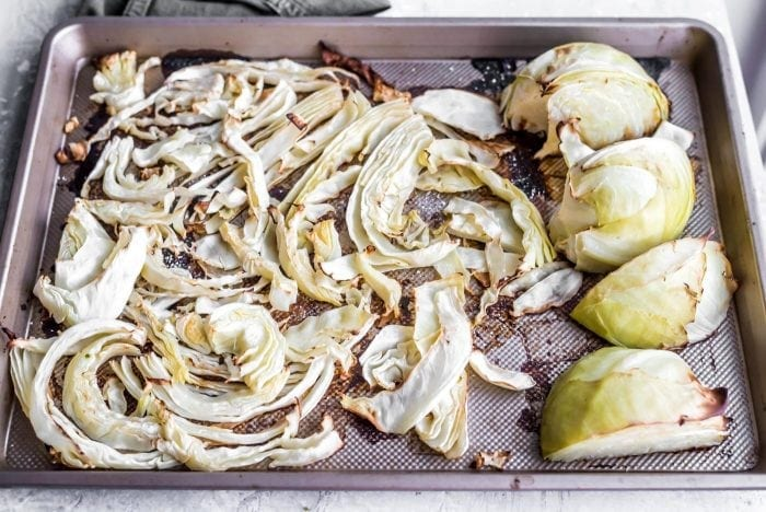 Shredded roasted cabbage and roasted cabbage chunks on a baking tray.