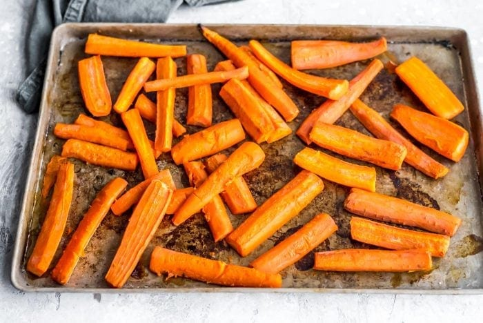 Roasted carrot chunks on a baking tray for vegan meal prep.