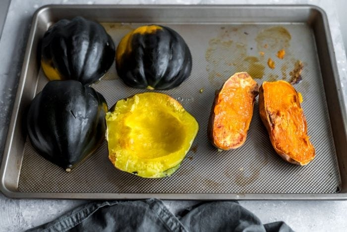 Roasted acorn squash and sweet potato on a baking tray.