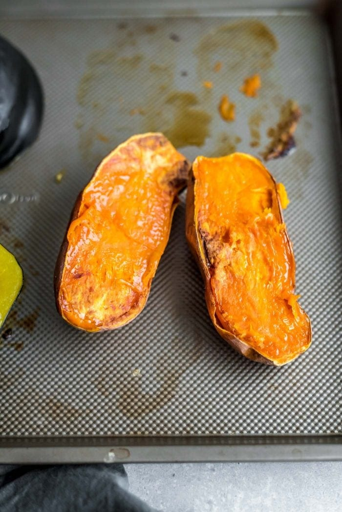 Roasted sweet potato and acorn squash on a silver baking tray.