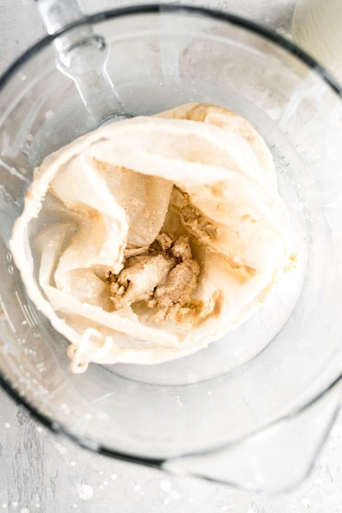 Leftover over oat milk pulp in a nut milk bag from making homemade oat milk.