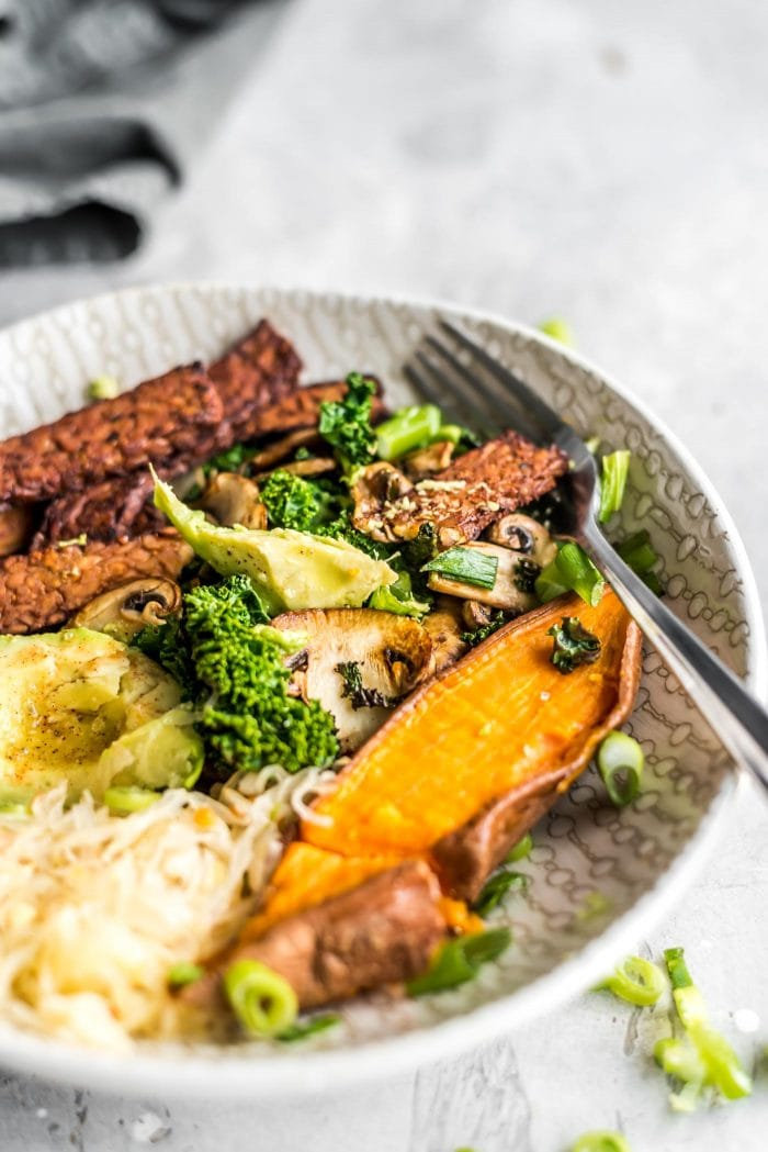 Sweet potato and sauerkraut in a vegan avocado breakfast bowl with tempeh bacon.