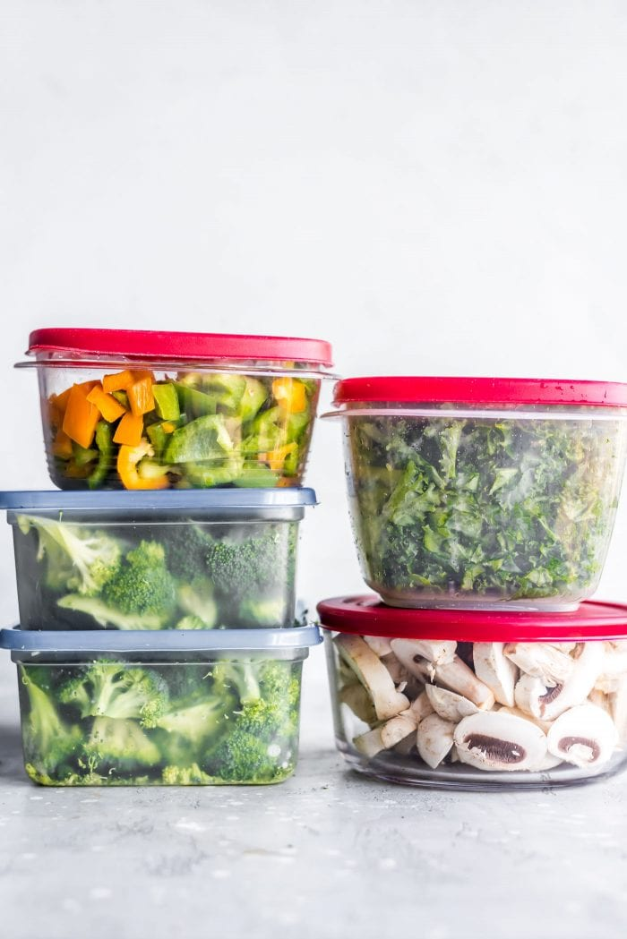 Containers of chopped, raw veggies packed up for vegan meal prep.