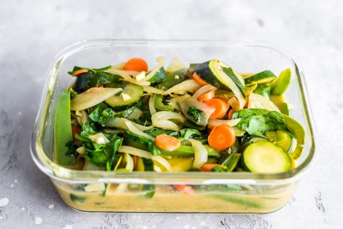 Healthy veggie green curry in a glass food storage container.