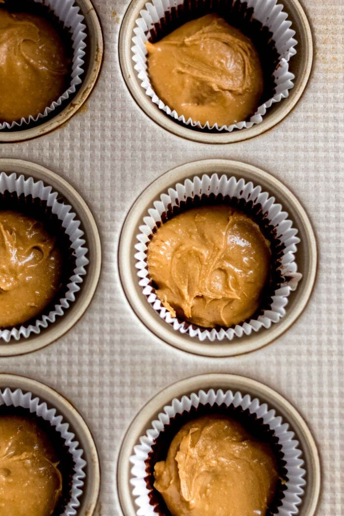 Overhead image of peanut butter spooned into a lined muffin tin.