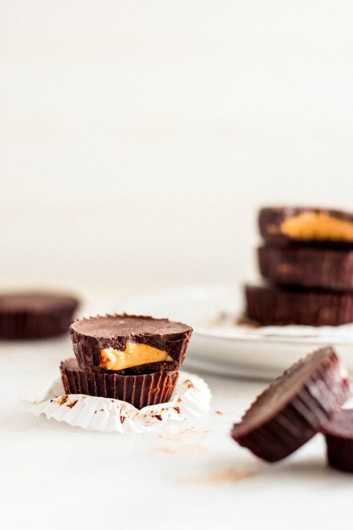 Two stacked chocolate peanut butter cups, one has a bit out of it to show inside. More cups in background.