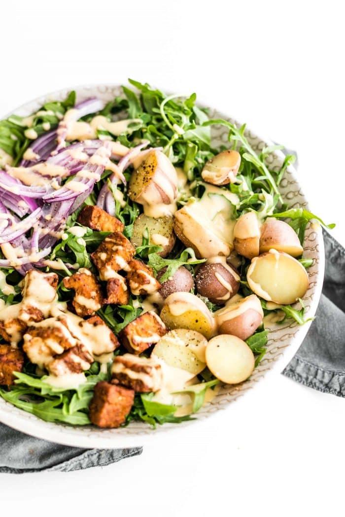 Warm potato arugula salad with tempeh, red onion and tahini dijon dressing.