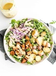 Warm potato arugula salad with tempeh and dijon tahini dressing.