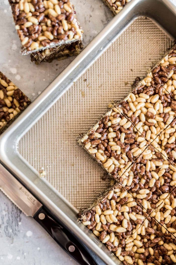 Healthy rice crispy treats cut into squares in a metal baking pan.