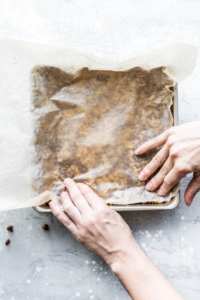 Using a piece of wax paper to flatten the sticky brown rice crispy mixture into a baking pan.