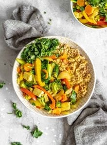 Quick and easy coconut veggie curry in a bowl with cilantro, tofu and rice.