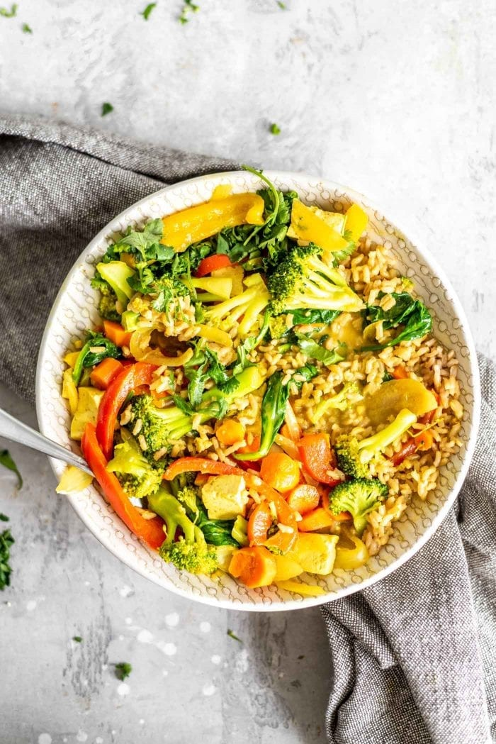 Veggie curry in a bowl with rice and tofu.