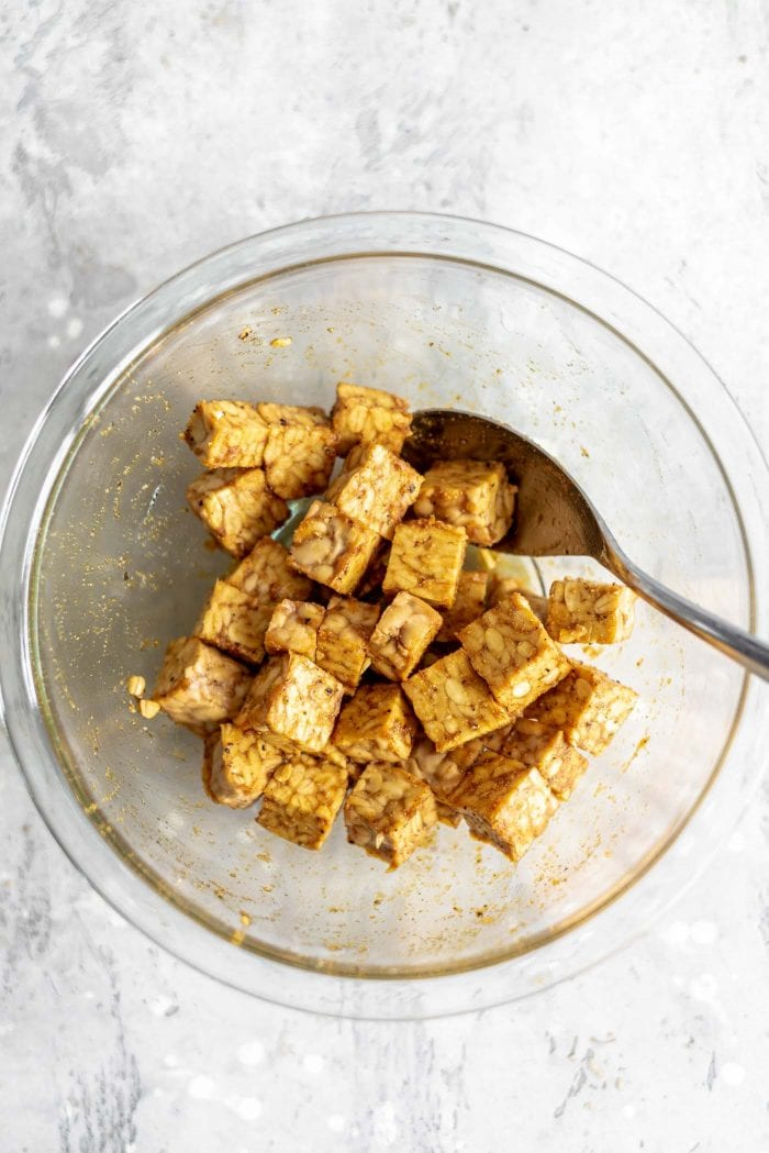 Cubed tempeh with soy sauce in a glass bowl.