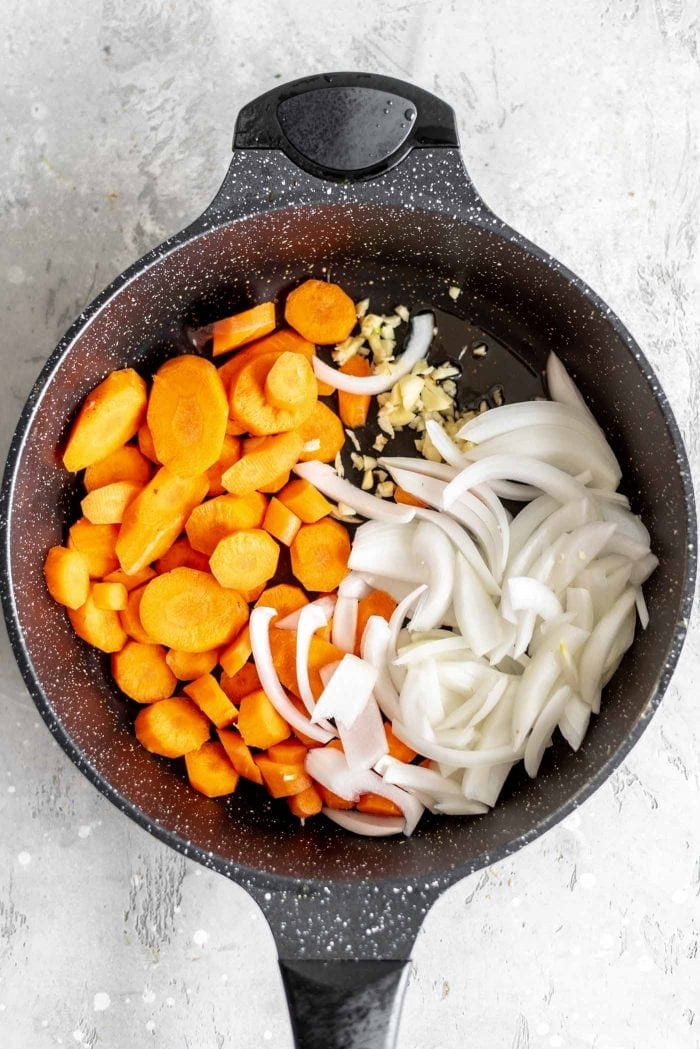 Chopped carrots, sliced onion and garlic in a skillet.