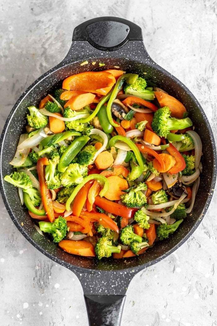 Mixed stir fried veggies in a skillet.