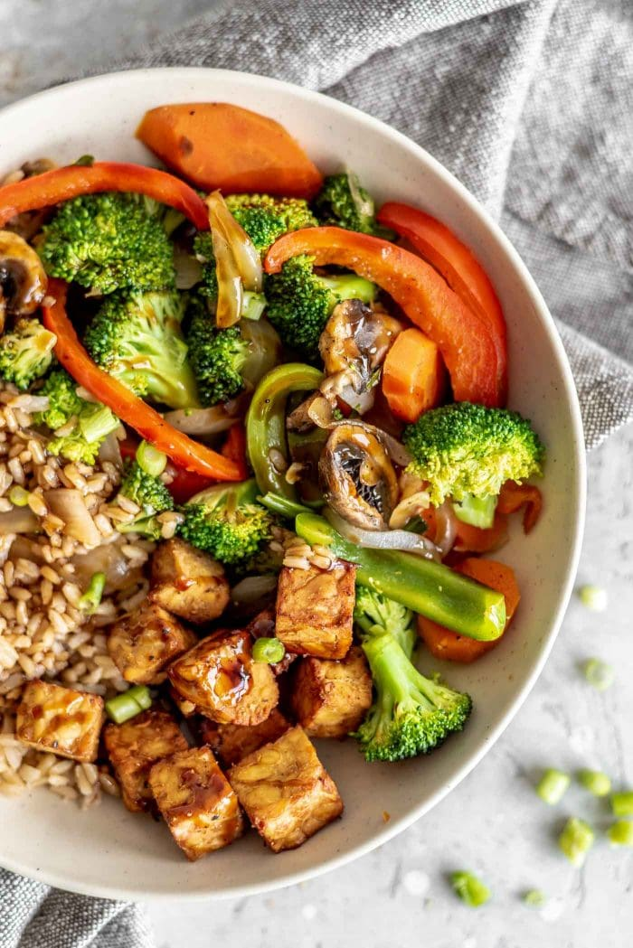Brown rice, tempeh and veggie stir fry in a bowl with hoisin sauce.
