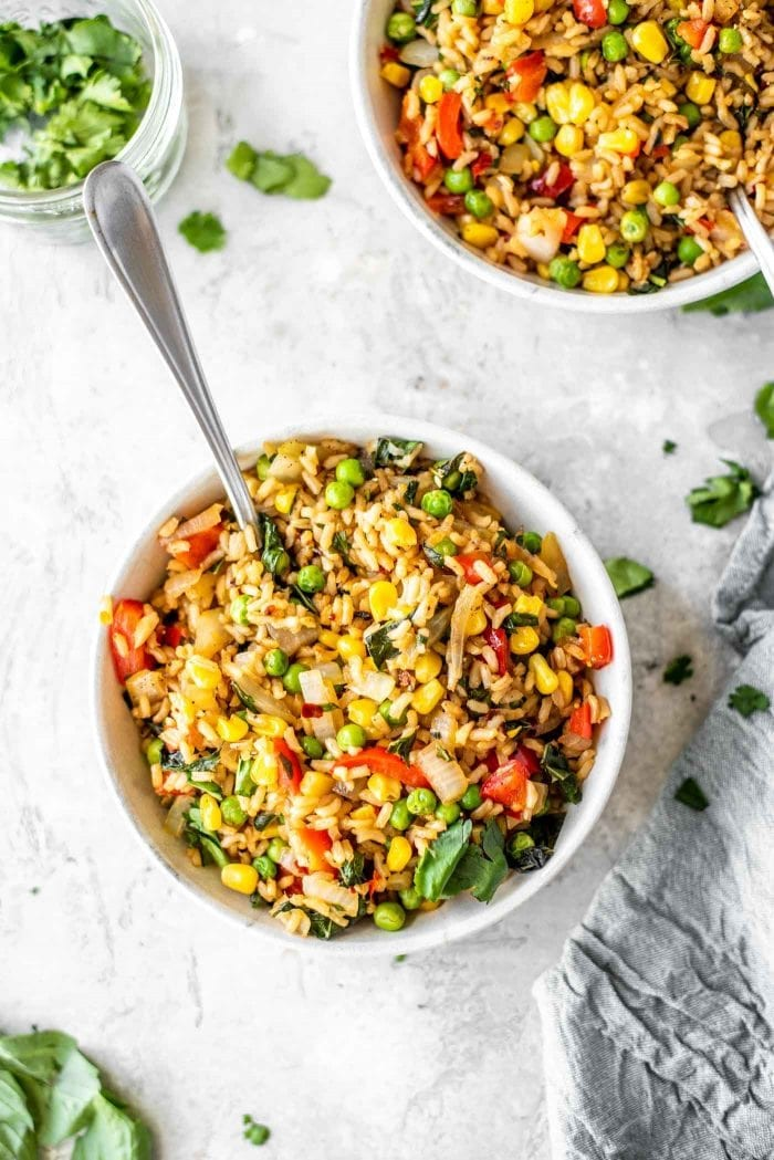 Two bowls of healthy vegan basil fried rice with peas, corn, onions and bell pepper.