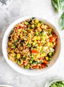 A white bowl filled with vegan basil fried rice with peas and corn.