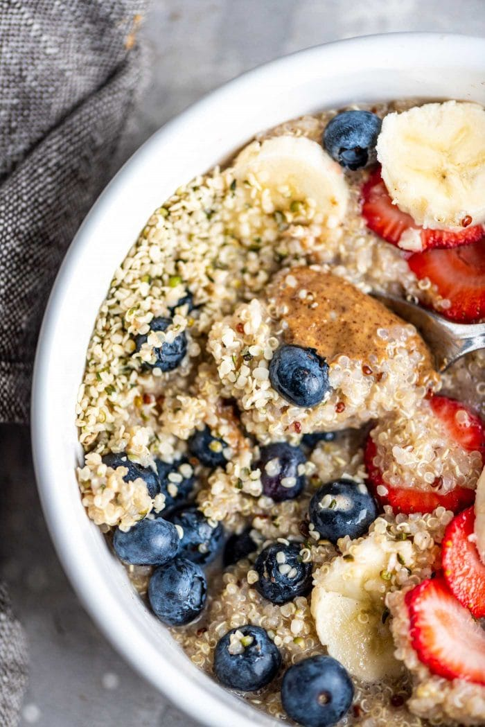 White bowl filled with quinoa topped with strawberries, blueberries and banana.