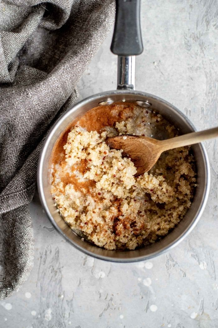 Cooked quinoa with cinnamon and almond milk in a small saucepan with a wooden spoon.